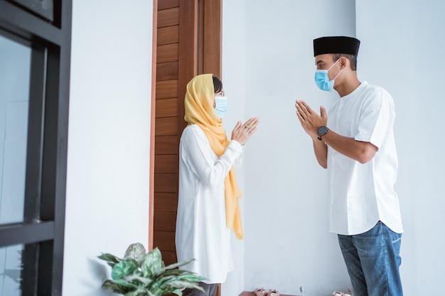 Retrato de um homem e uma mulher visitando sua casa durante o eid mubarak usando máscara médica para se proteger do covid 19 e manter o distanciamento social