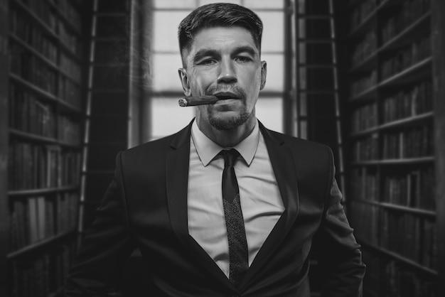 Retrato de um homem elegante de terno com um charuto. conceito de negócios. mídia mista