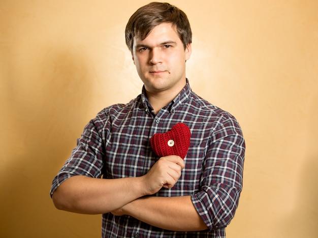 Retrato de um homem elegante segurando um coração vermelho no peito