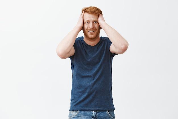 Retrato de um homem em desespero sentindo arrependimento, parado ansioso sobre uma parede cinza, cerrando os dentes, segurando as mãos na cabeça e franzindo a testa
