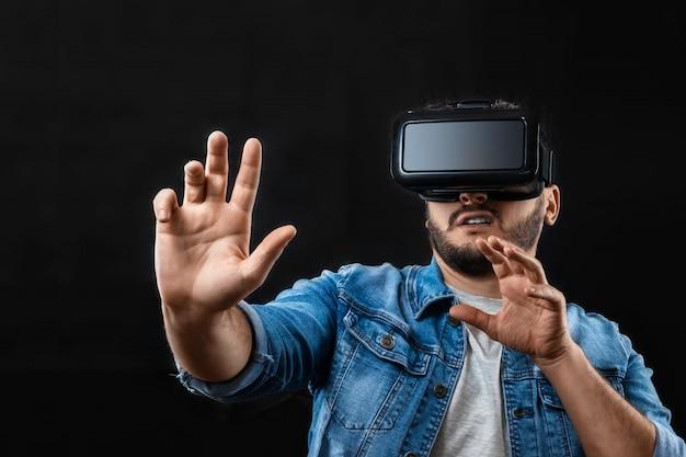Retrato de um homem em óculos de realidade virtual, vr, contra um fundo escuro.