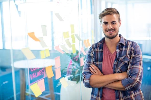 Retrato de um homem em pé ao lado das notas adesivas na parede do escritório