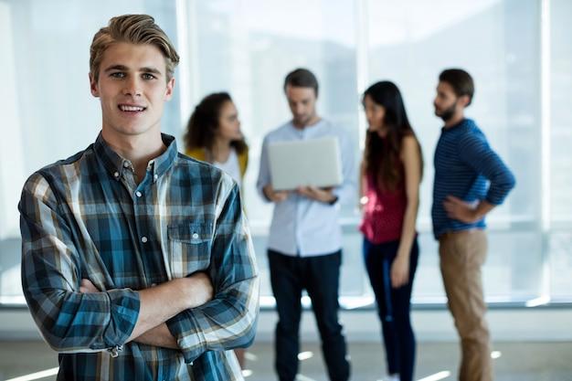 Retrato de um homem em pé com os braços cruzados no escritório enquanto um colega discutindo atrás