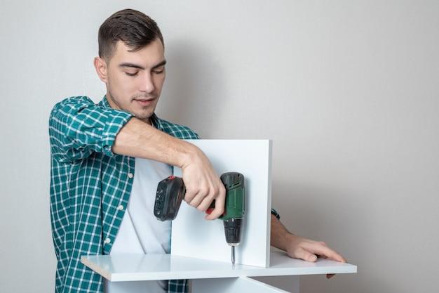 Retrato de um homem em roupas casuais em uma chave de fenda elétrica