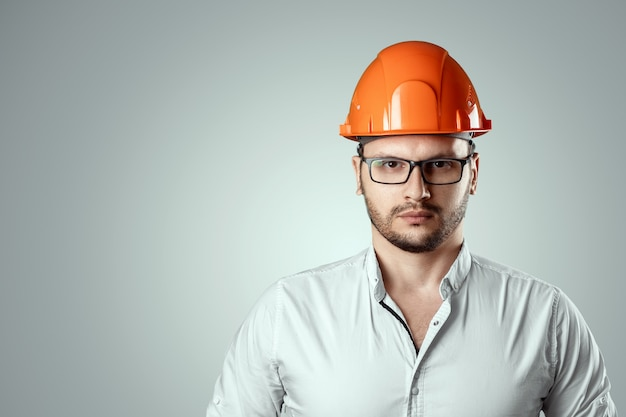 Retrato de um homem em um capacete de construção laranja. arquitetura de conceito, construção, engenharia, design, reparação. espaço da cópia