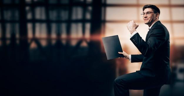Retrato de um homem em um terno de negócio. ele está de pé no aeroporto com as mãos para cima