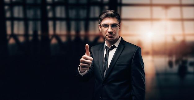Retrato de um homem em um terno de negócio. ele está parado no aeroporto com o dedo levantado.