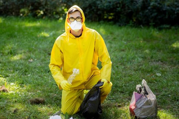 Retrato de um homem em um traje de proteção amarelo e máscara.