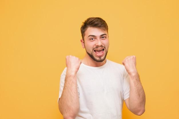 Retrato de um homem emocional feliz com uma barba, se alegra com a vitória em um amarelo
