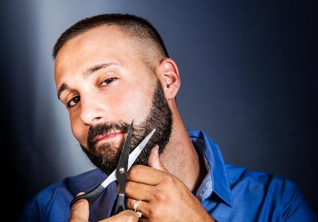 Retrato de um homem enfeitando sua barba com uma tesoura