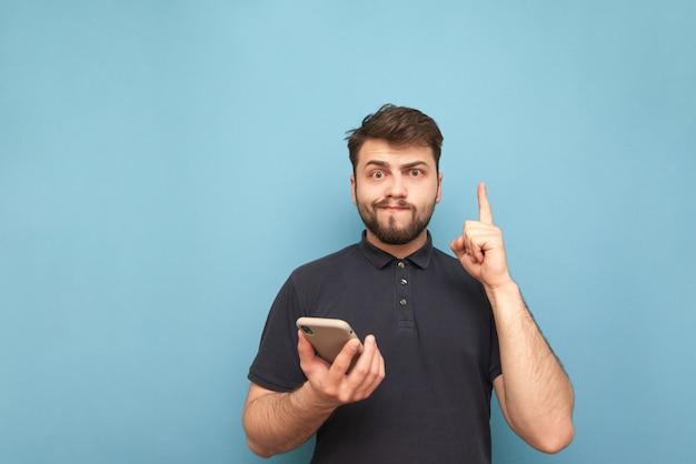Retrato de um homem engraçado com uma barba e um telefone na mão azul e fazendo uma careta.