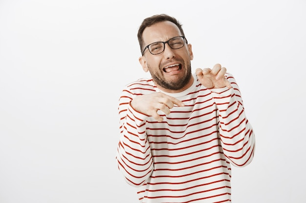 Retrato de um homem engraçado e emotivo de óculos fazendo caretas e imitando patas de dinossauro com as mãos no peito