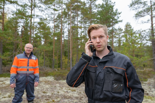 Retrato de um homem escandinavo maduro e um jovem escandinavo pronto para a colheita na floresta juntos ao ar livre
