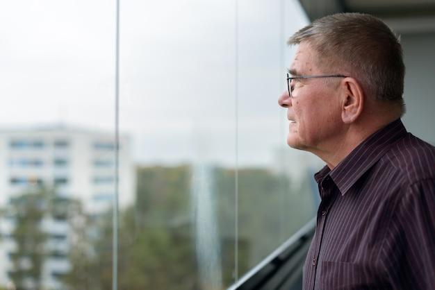 Retrato de um homem escandinavo sênior com cabelo grisalho, usando óculos, olhando pela janela dentro de casa