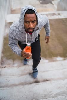 Retrato de um homem esporte subindo escadas ao ar livre. conceitos de fitness, esporte e estilo de vida saudável.