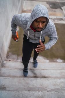 Retrato de um homem esporte subindo escadas ao ar livre.