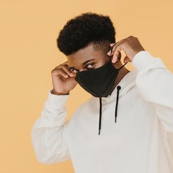 Retrato de um homem estiloso colocando máscara facial