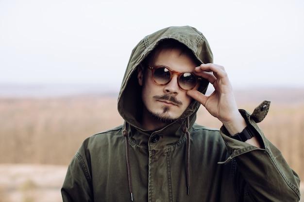 Retrato de um homem estiloso com bigode e barba em óculos de sol nas montanhas