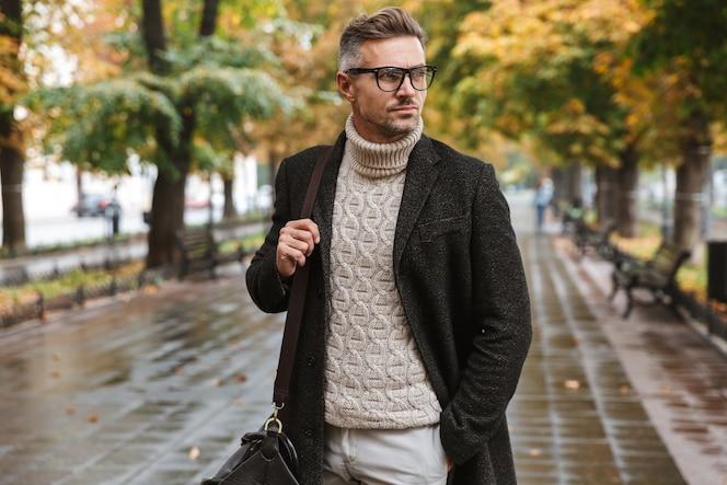 Retrato de um homem estiloso com óculos dos anos 30, caminhando ao ar livre pelo parque de outono