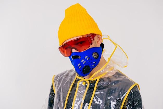 Retrato de um homem estranho elegante com máscara e capa de chuva posando sobre uma parede branca