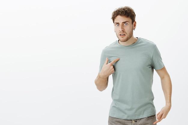 Retrato de um homem europeu bonito chocado e frustrado com brincos, apontando para si mesmo com o dedo indicador e franzindo a testa, fazendo perguntas