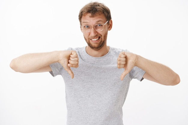 Retrato de um homem europeu fofo e engraçado descontente de óculos e camiseta cinza mostrando os polegares para baixo e fazendo caretas de antipatia, expressando desaprovação estando insatisfeito