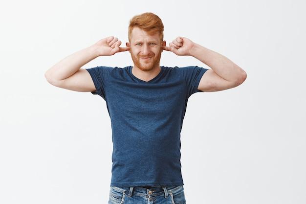 Retrato de um homem europeu forte e atraente descontente com cabelos ruivos, cobrindo as orelhas, franzindo a testa e franzindo os lábios de desconforto, sendo irritado com o som alto