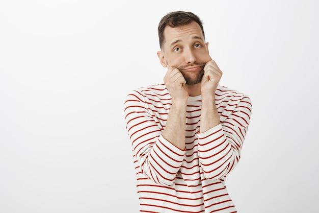 Retrato de um homem europeu simpático e fofo em um pulôver listrado casual, segurando as bochechas com as palmas das mãos e fazendo caretas, parecendo chateado ou entediado