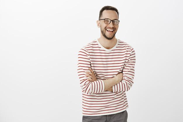 Retrato de um homem europeu tímido e bonito com barba em óculos, cruzando as mãos sobre o peito e rindo alto, sentindo-se bem enquanto conversa casualmente com um novo grupo de amigos sobre a parede cinza