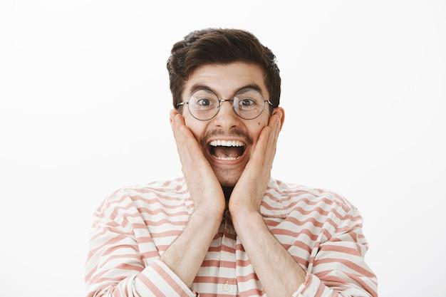 Retrato de um homem fascinado e feliz com bigode, gritando de felicidade e surpresa, segurando as palmas das mãos nas bochechas, ficando impressionado e surpreso ao ver o incrível ator famoso sobre a parede cinza