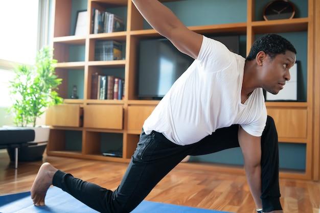 Retrato de um homem fazendo exercícios enquanto fica em casa