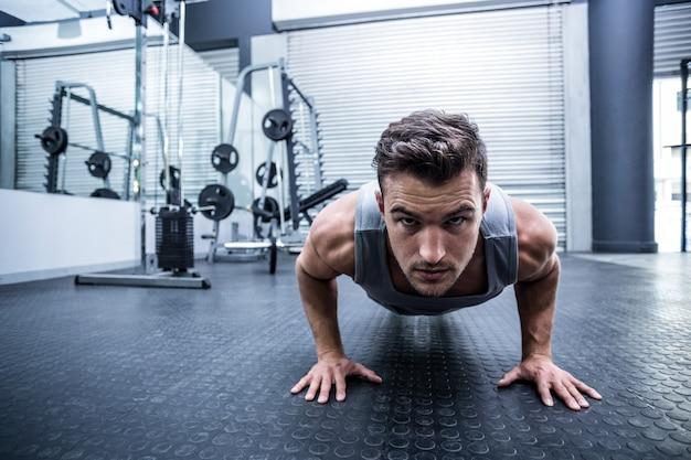Retrato, de, um, homem, fazendo, um, pushups, em, a, crossfit, ginásio