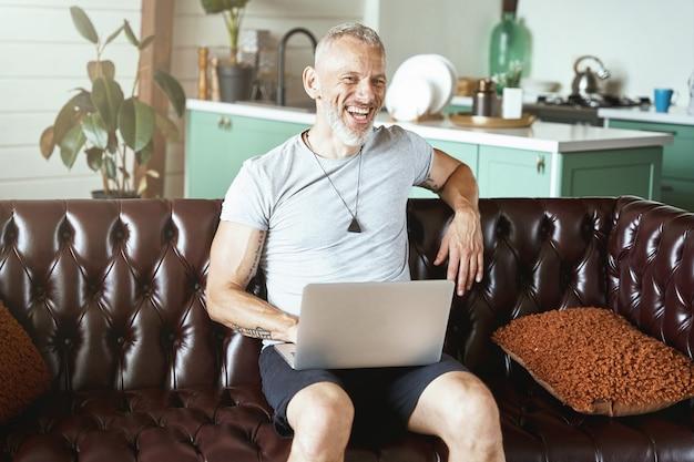Retrato de um homem feliz, caucasiano, de meia-idade, vestindo roupas casuais, usando laptop enquanto está sentado