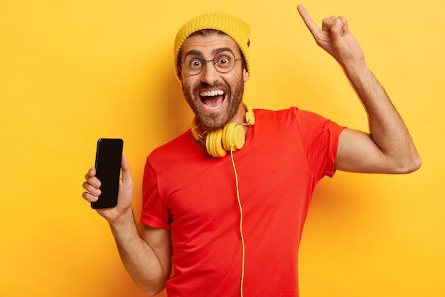 Retrato de um homem feliz com a barba por fazer segura o celular com a tela vazia, levanta o braço e aponta com o dedo indicador acima, tem uma expressão facial alegre, usa chapéu amarelo e camiseta vermelha, usa fones de ouvido