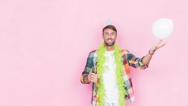 Retrato de um homem feliz com balão branco em fundo rosa