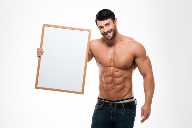 Retrato de um homem feliz com torso musculoso, segurando uma placa em branco isolada em uma parede branca