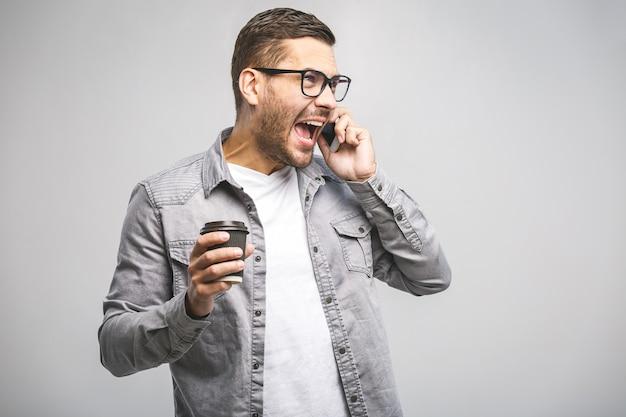 Retrato de um homem feliz confiante segurando o telefone móvel e comemorando o sucesso isolado sobre fundo branco