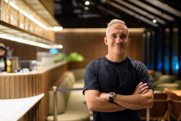 Retrato de um homem feliz dentro da cafeteria à noite, sorrindo com os braços cruzados, foto horizontal
