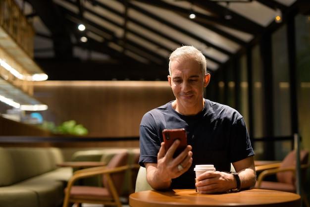 Retrato de um homem feliz dentro de uma cafeteria à noite, usando um telefone celular, foto horizontal