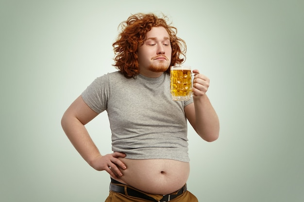 Retrato de um homem feliz e alegre de gengibre, sentindo o cheiro de cerveja espumosa fria em suas mãos