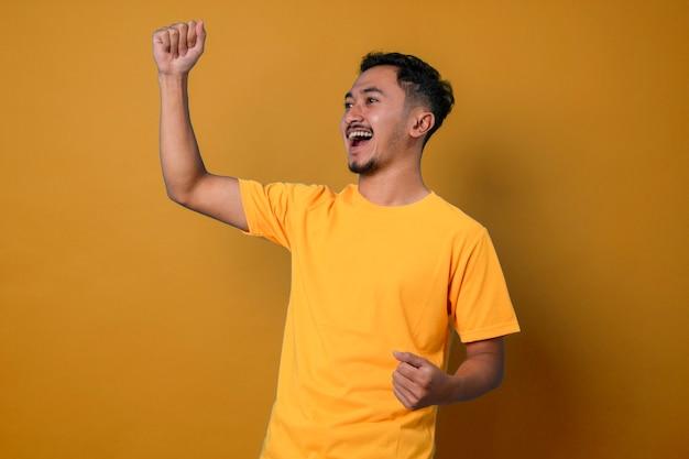 Retrato de um homem feliz e atraente animado com a boca bem aberta e os braços erguidos em um fundo amarelo