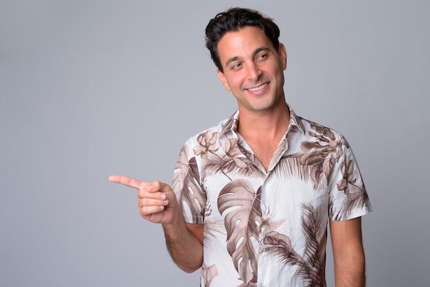 Retrato de um homem feliz e bonito turista hispânico apontando o dedo para o lado
