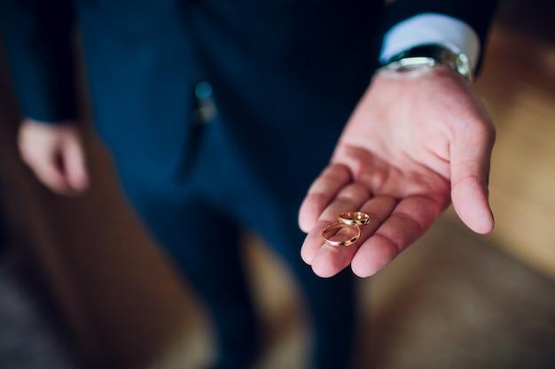 Retrato de um homem feliz e bonito vestido de smoking segurando a caixa aberta com um anel de noivado.