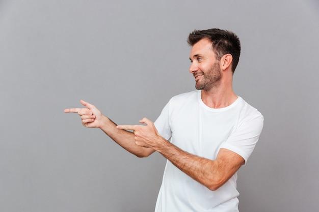 Retrato de um homem feliz e casual apontando os dedos para longe sobre um fundo cinza