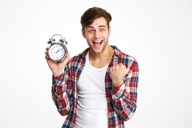 Retrato de um homem feliz e satisfeito, segurando o despertador