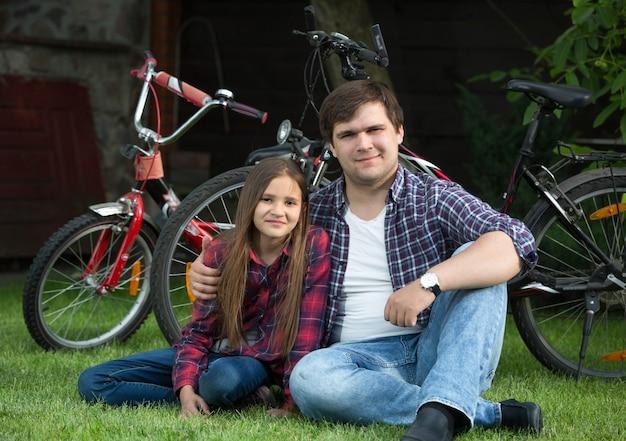 Retrato de um homem feliz e uma jovem relaxando no parque depois de andar de bicicleta