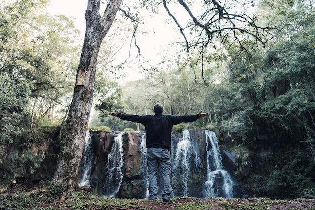 Retrato de um homem feliz em pé se divertindo com os braços estendidos na frente de uma cachoeira.