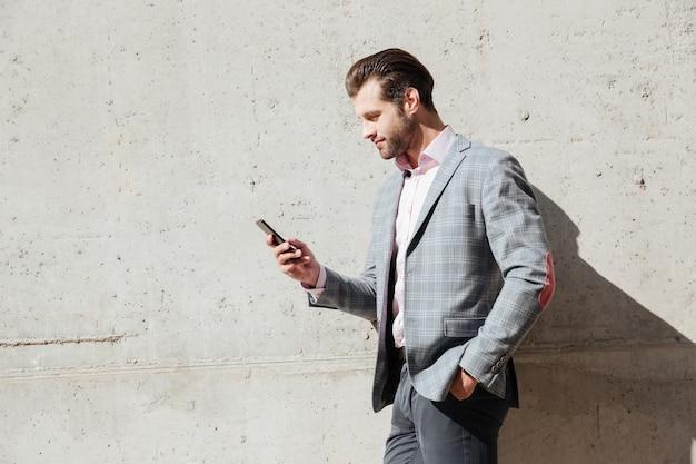 Retrato de um homem feliz na jaqueta segurando o telefone móvel