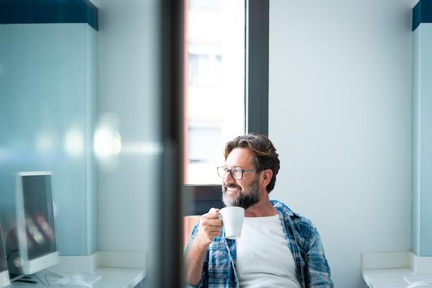 Retrato de um homem feliz, olhando pela janela e sorrindo, bebendo um café em casa ou no escritório - adulto homem caucasiano com barba e óculos sozinho na atividade de pausa no trabalho - pessoas felizes com óculos