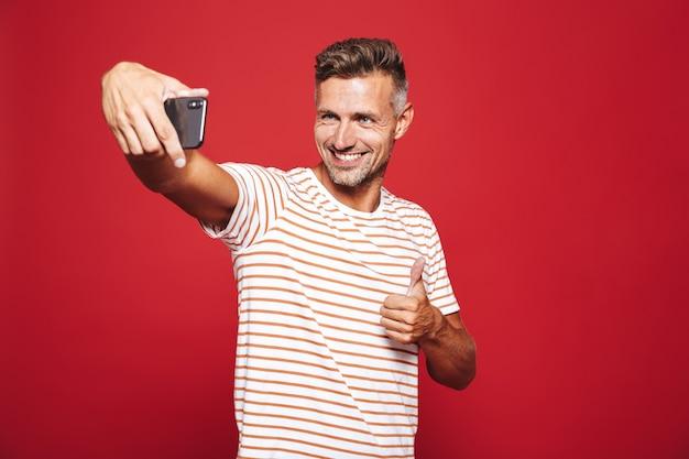 Retrato de um homem feliz parado no vermelho